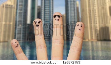 gesture, family, travel, tourism and body parts concept - close up of four fingers with smiley faces over dubai city infinity edge pool background