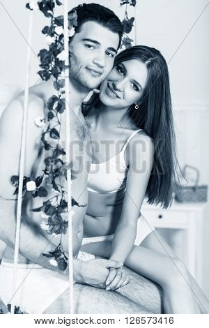 Young love couple sitting on the swing in bedroom