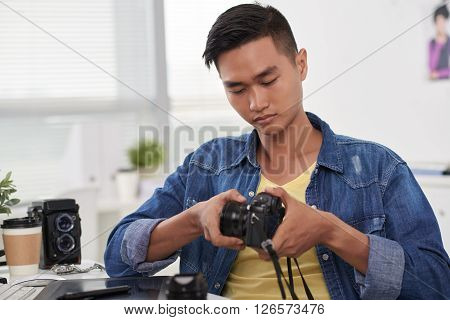 Young Asian photographer changing lens of his camera