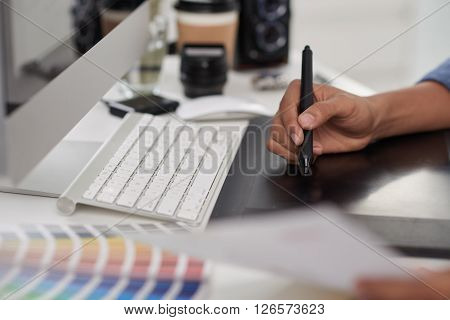 Hand of graphic designer using stylus and tablet