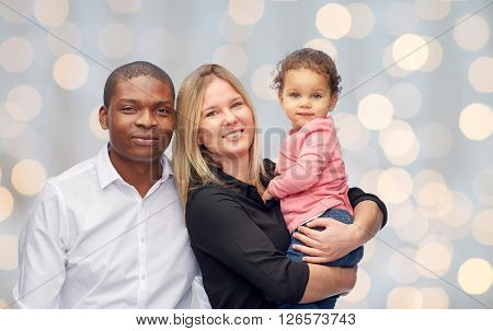 family, children, race and nationality concept - happy multiracial mother, father and little child over holidays lights background