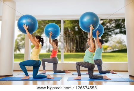 pregnancy, sport, fitness, people and healthy lifestyle concept - group of happy pregnant women exercising with ball in gym over natural window view background