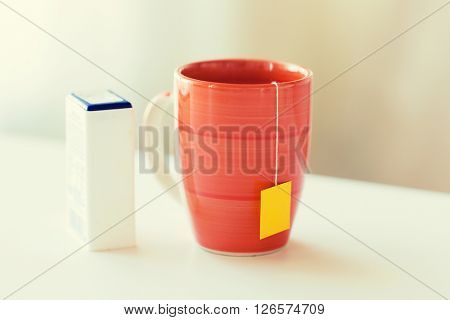 food, junk-food, drinks and unhealthy eating concept - close up of sweetener and cup with tea bag on table