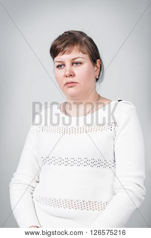 Adult sad woman with overweight on the gray background