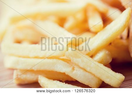 junk-food, fast food and eating concept - close up of french fries on table