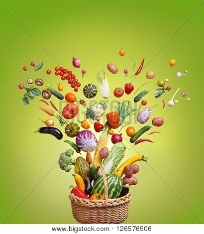 Healthy food in basket. Studio photography of different fruits and vegetables on green background top view. High resolution product.