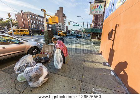 NEW YORK USA - OCT 21 2015: woman poses garbage at the street in Brooklyn New York. Poverty is a main social issue in New York and many people live from collecting garbage.