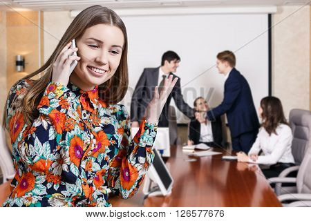 Business woman speak on the phone foreground and business people shaking hands, finishing up a meeting