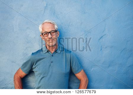 Mature Man Standing Against A Blue Wall