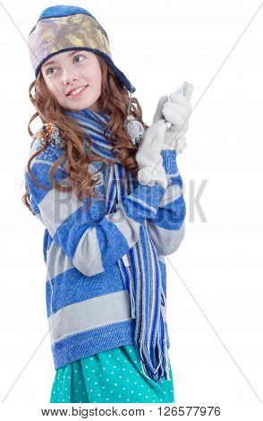 Pretty teen girl in winter clothes with smartphone on white background
