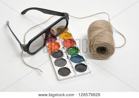 Flat lay of art scene featuring of thread twine, glasses and watercolor paints isolated on a white background. Art design.