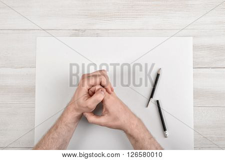 Closeup masculine folded hands on wooden panel with white paper and broken black pencil in top view. Worry process.
