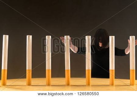 Woman standing behind a row of cigarettes as a concept of a prisoner of the addiction having in smoking.