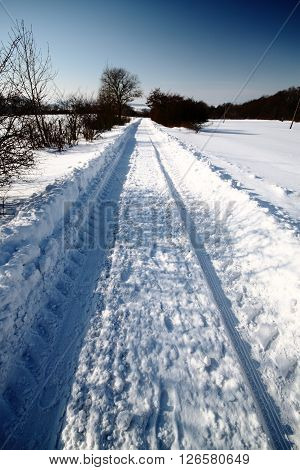 Rural road in the deep snow furrow