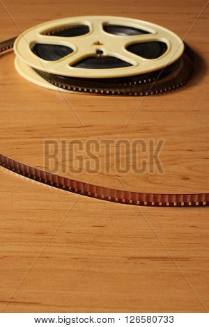 Reel with eitght millimeter film on the wooden table