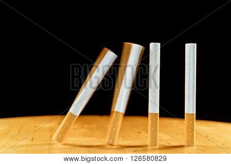 Cigarettes domino falling as a concept of the addiction that cigarettes create. One cigarette brings another and the addiction continues.