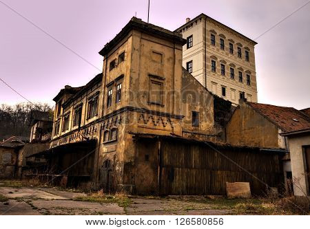 Desolated old large brewery building with dirty yard