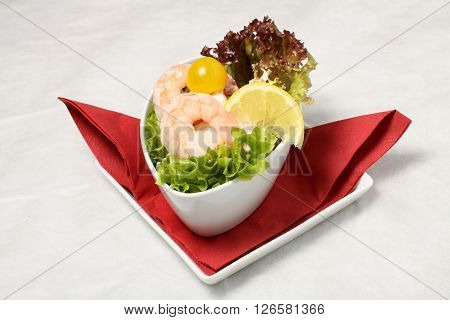Small salad with clams and lemon on red triangle