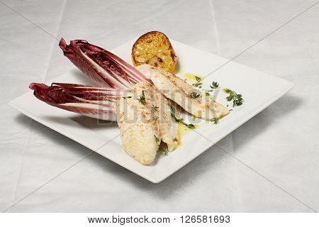 White carp meat with chicory and baked lemon