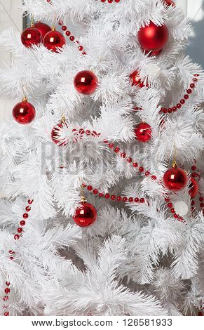 White artificial christmas tree with red decoration