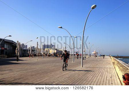 TEL AVIV, ISRAEL - APRIL 1, 2016: Israeli man ride bike on sea promenade in Tel Aviv, Israel. Panoramic view.