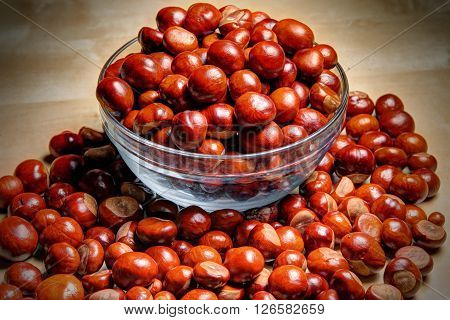 Glass bowl of chestnuts on the chestnuts heap