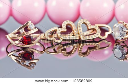 Various Golden ornaments on a background of pink beads ** Note: Shallow depth of field