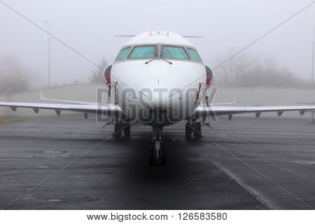 Front part of the white medium size jet parked in the fog