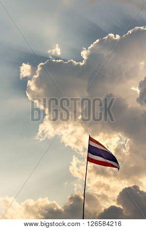 Thai nation flag on wooden pole and sunbeam
