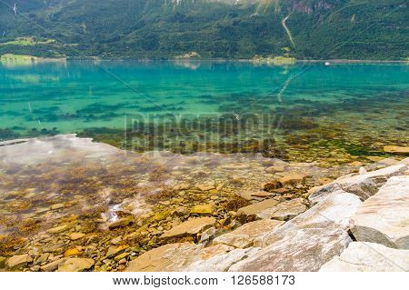 Norwegian stony fjord coast and colorful transparent water