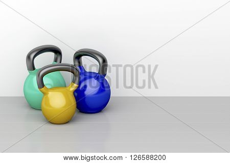 Three kettlebells of different size on shiny gray floor in the fitness center, 3d illustration