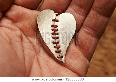 broken heart stitched with red thread on a hand