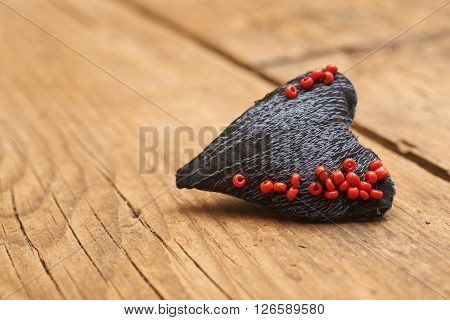heart made of cloth with red beads on old wood with copy space concept about love at Christmas Mother's Day or Valentine's Day
