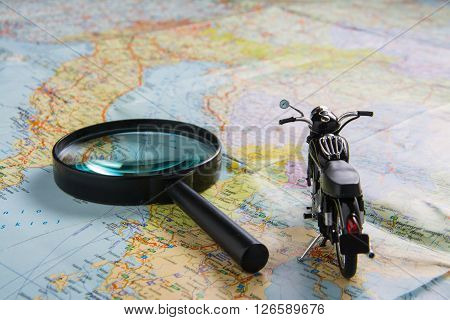classic black motobike on map. travel planning.