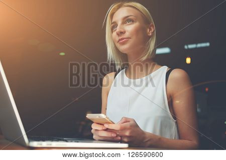 Young beautiful blonde female holding mobile phone while sitting with portable net-book in coffee shop interior charming dreamy woman using cell telephone and laptop computer during rest in cafe