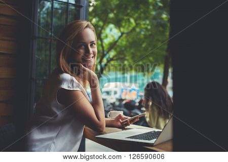 Young happy charming female posing while holding mobile phone attractive woman relaxing after work on laptop computer while sitting in cafe smiling lady using technology during rest in coffee shop