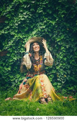 smiling young woman in boho style long  dress and hat sit on grass in garden full body shot