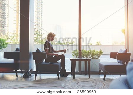 Young confident female freelancer is using laptop computer for distance work during her trip abroad while is sitting in co-working cafe against window with copy space background for your advertising