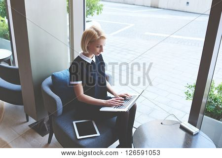 Young woman skilled trader is considering customer order via laptop computer while is sitting in modern co-working space. Blonde female restaurant owner is using portable net-book during work day
