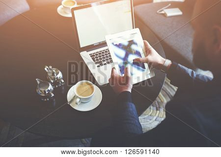 Businessman is holding digital tablet with world map on the screen while is sitting with net-book in cafe. Closeup of male CEO is using digital tablet and laptop computer during work break
