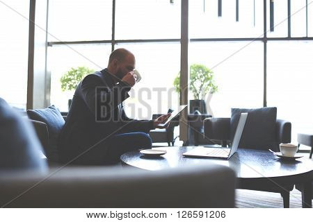 Man skilled economist is considering enterprise scheme by using touch pad while sitting with net-book in cafe. Male employer is drinking coffee and reading resume before interview with specialist