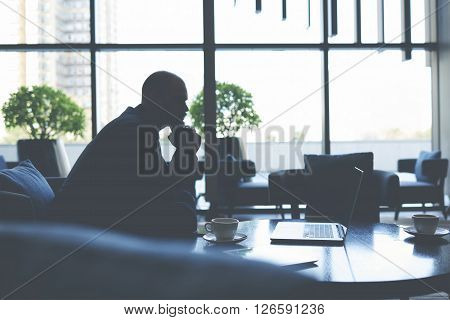 Silhouette of a businessman is thinking about future conversations with investors while is sitting in cafe with net-book. Male financier is watching financial news in internet via laptop computer