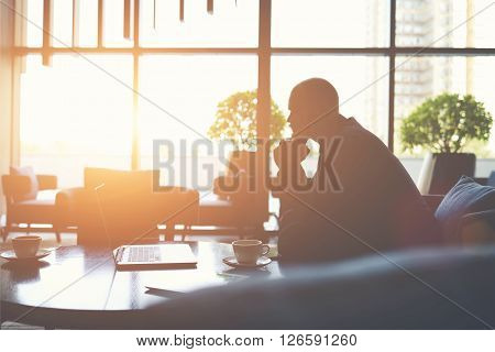 Silhouette of man managing director is thinking how to prevent the company's crisiswhile is sitting with net-book in cafe. Male financier in watching world news on laptop computer during coffee break