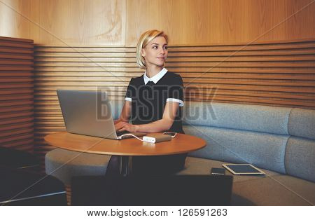 Female entrepreneur is looking awaywhile is waiting file download of confidential information about her enterprise on laptop computer.Woman lawyer is using net-book for prepare to meeting with client