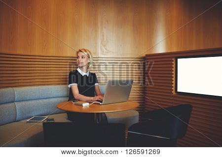 Businesswoman is looking on partner which she expect in modern co-working space with laptop computer. Successful female managing director is using net-book while is sitting near screen with mock up