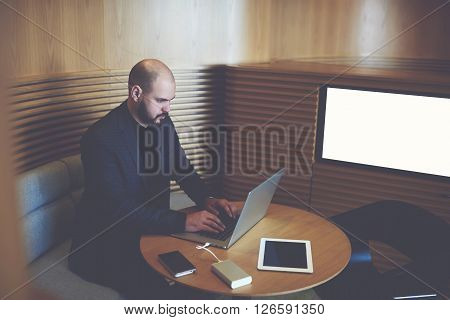 Young managing director is writing an advertisement on the Internet through a laptop computer about finding financial expert while is sitting in office interior near screen with mock up copy space