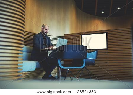Serious businessman in luxury suit is working on laptop computer while is sitting in modern co-working space near screen with mock up copy space for your advertising text message or information