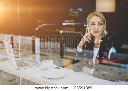 Woman freelancer is talking on mobile phone with her boyfriend while is sitting in urban coffee shop at the table with open portable laptop computer cup of cappuccino and dessert. Female student
