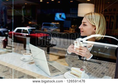 Pretty hipster girl with mobile phone in hands is thinking about university project while is waiting file download on portable laptop computer during morning breakfast in urban freelance coffee house