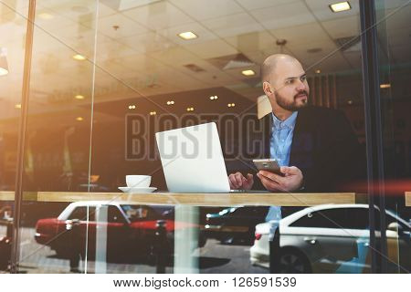 View through window of male skilled managing director with net-book and mobile phone in hands is waiting client for a planned meeting in cafe. Young businessman is using cell phone and laptop computer